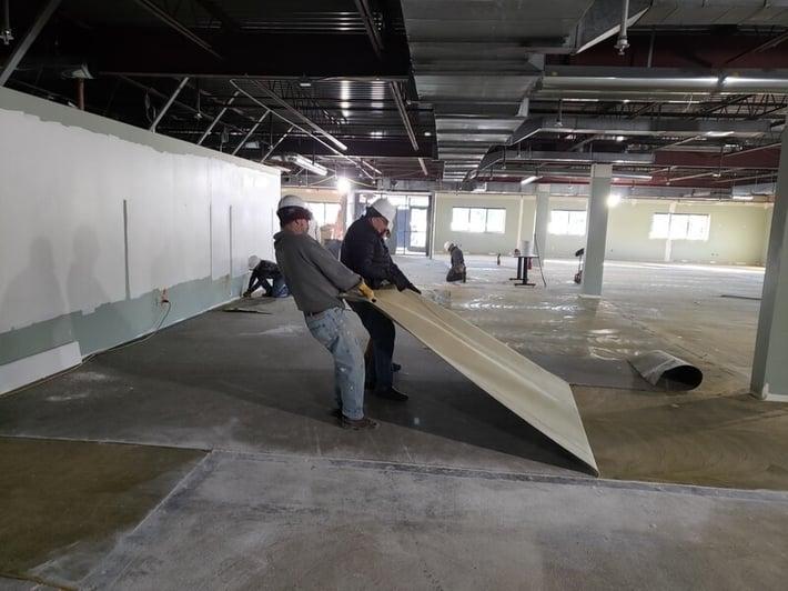 Volunteers pull up flooring.