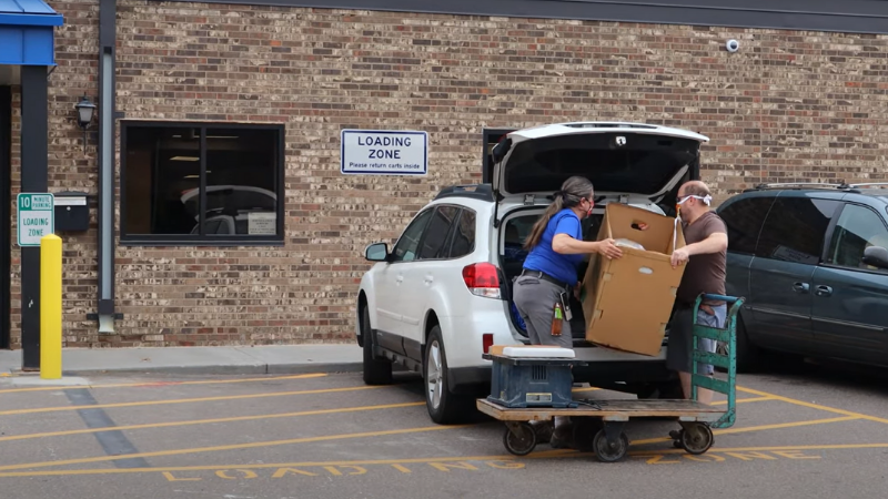 Two people loading a car's trunk at the ReStore in New Brighton.