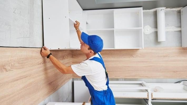 Homeowner installing kitchen cabinets.