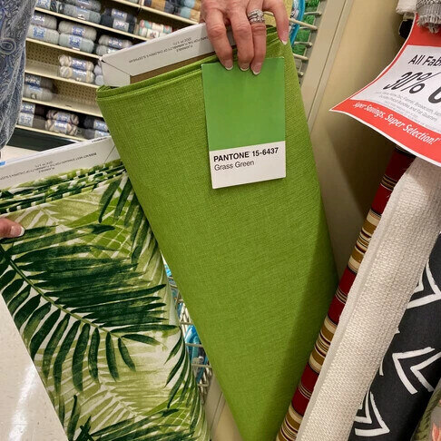 """A new lime green bolt of fabric, labeled """"Pantone 15-6437 - Grass green."""""""