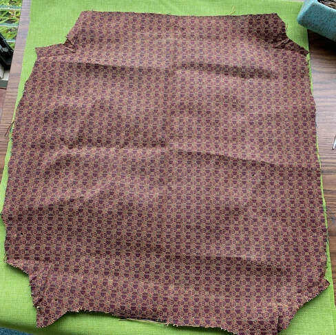 The old upholstery fabric laid on top of the new.