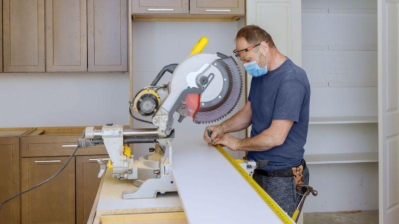 Measuring lumber next to a circular saw.
