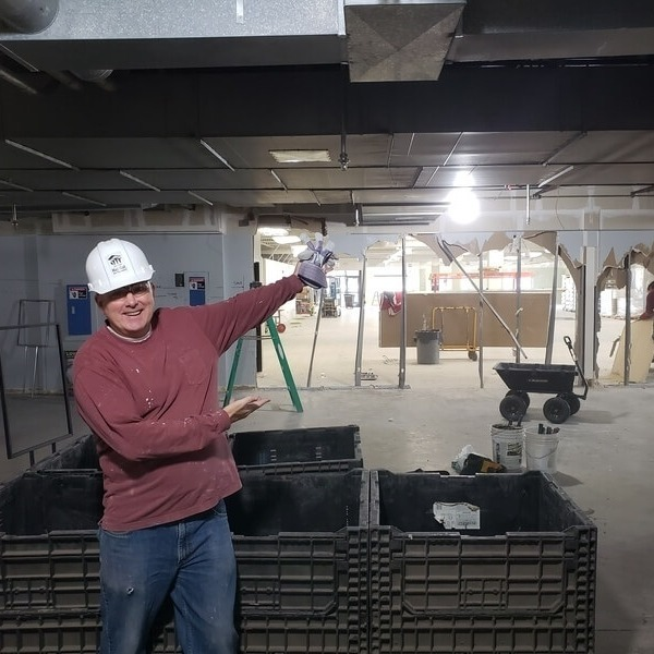 ReStore Director Pete O'Keefe in a red shirt, jeans, and a white hardhat, showing off the ongoing construction at the ReStore. Behind him are many stacked plastic boxes, and a wall that's been mostly demolished.