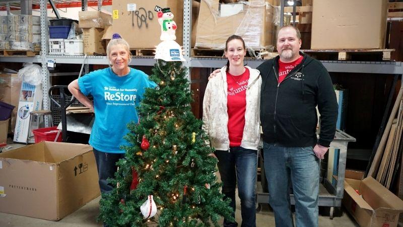ReStore volunteers behind a small Christmas tree.