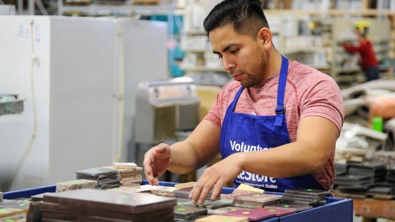 A ReStore volunteer sorting tiles.